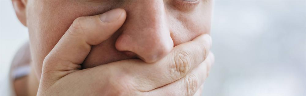 Homme qui cache sa mauvaise haleine avec sa main